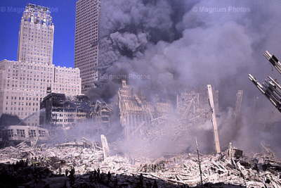 Notice that dark smoke is emanating from a number of windows on the south face of WTC7. Also note that while smoke is emanating from the south face of most of the SW corner offices, only a few windows of the western face of the same corner offices are emitting smoke. Finally, note that there is dark smoke billowing from WTC5 and WTC6, which are in the foreground of the photo, at the foot of WTC7. WTC6 (on the left) is being sprayed with water by firefighters on the scene.