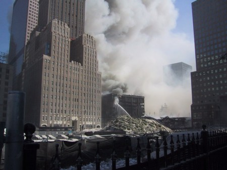 Note that WTC6 is on fire and is being sprayed with water by the FDNY, while a large cloud of emanates from its roof.
