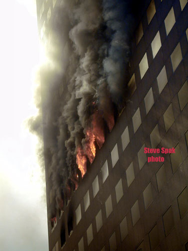 A close-up of the lower portion of the eastern face of WTC 7 with a fire on the 12th floor.