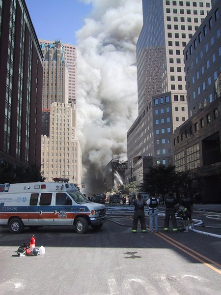 Take note of the fact that there are at least three sources contributing to the large smoke cloud that is lingering between the buildings in this photo: Smoke emanating from the south face of WTC7, as well as fires in WTC5 & WTC6. Also take note of the fact that smoke is billowing from the roof of WTC6 and that it is being sprayed with water by firefighters on the scene.