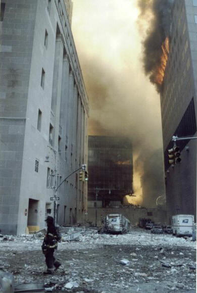 The lower portion of the eastern wall of WTC 7, as seen from the corner of Barclay Street & West Broadway. In the background, WTC5 (left) and WTC6 (right) are on fire and smoking.