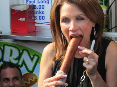 Michelle Bachmann begins to take a bite of a corn dog, while at the Iowa State Fair