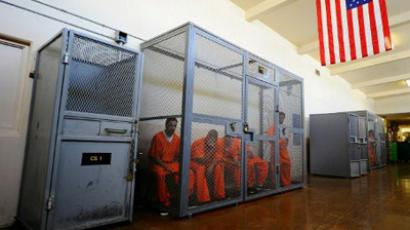 Caged Prisoners in Orange Jumpsuits