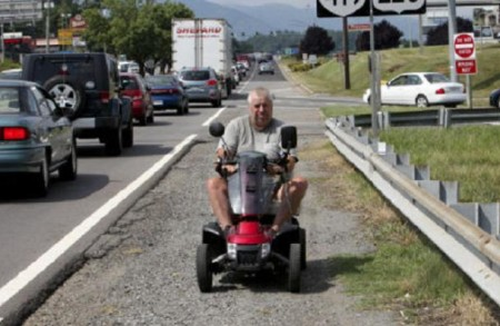 Larry Dodson rides his mobility scooter against traffic, as a pedestrian (photo by Stephanie Klein-Davis of The Roanoke Times)