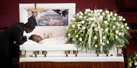 Franclot Graham speaks to his son, Ramarley Graham, in his casket before funeral services