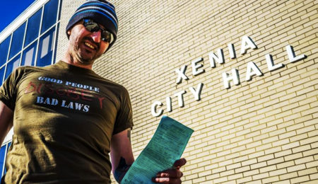 "Virgil Vaduva stands outside of Xenia City Hall in Ohio with a ticket he received for ""panhandling"" in his effort to raise money for charity"