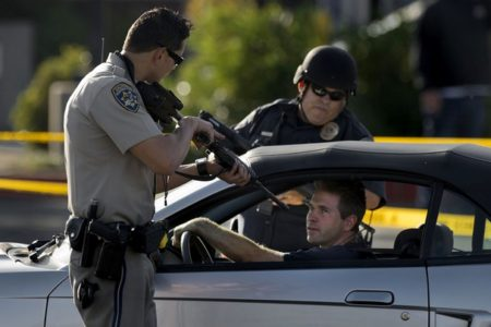 "Police officer points a loaded rifle at the head of an innocent motorist during a ""check point"" in Sacramento"