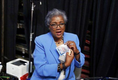 Donna Brazile holds up her CNN DNC pass